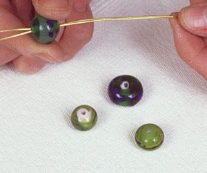 Infilare le perle per il ciondolo fai da te